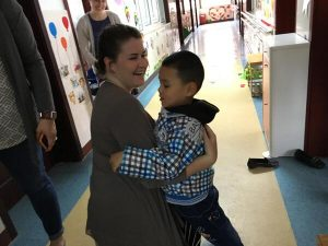 Saint Vincent student hugging child at Children Welfare Institute