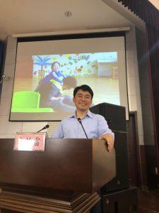Dr. Li smiling at podium