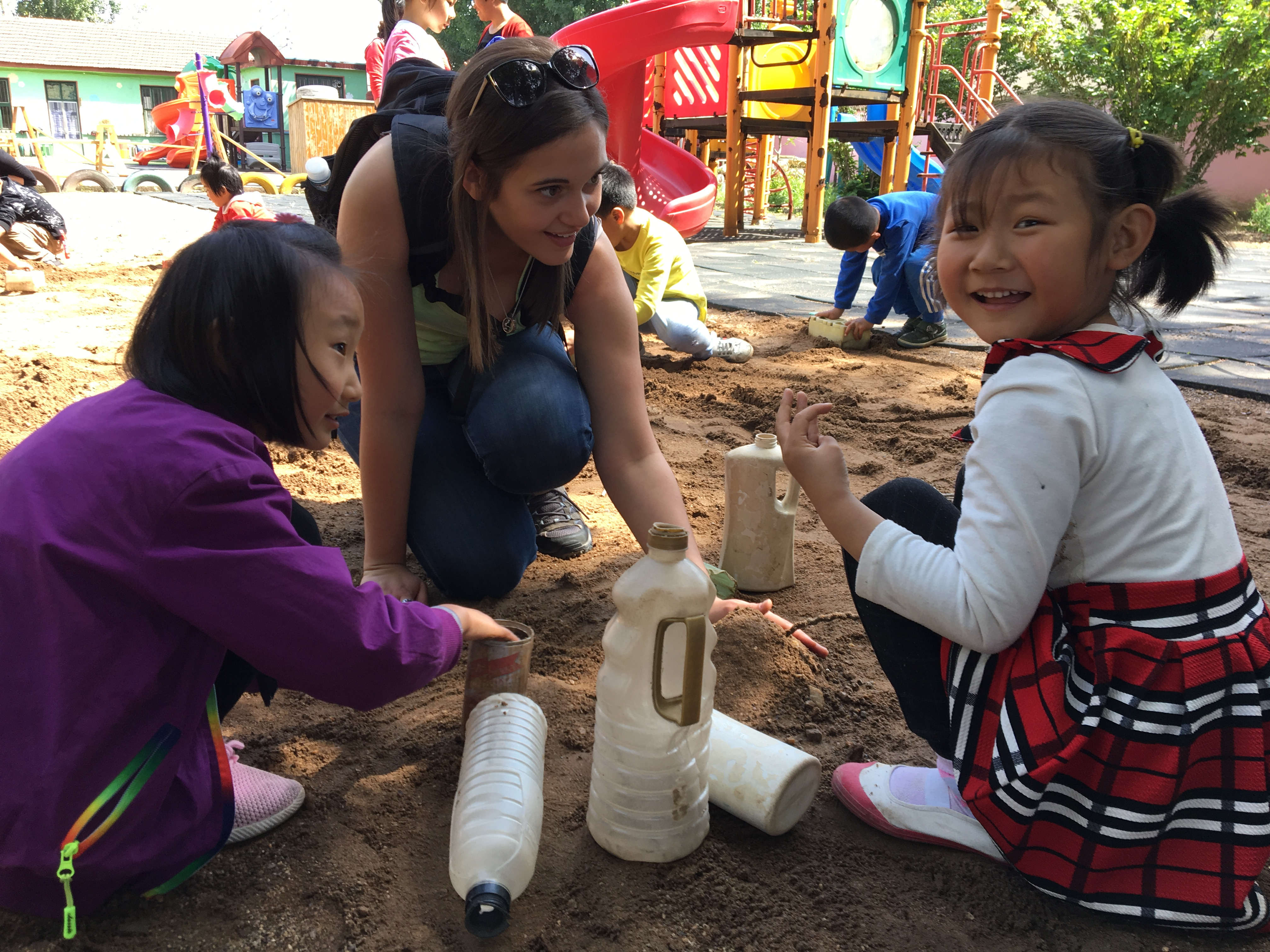 Chinese students playing in the sand with Saint Vincent student
